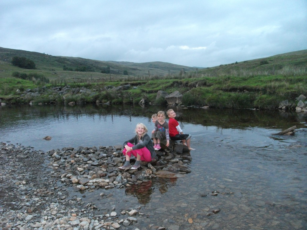 four children sitting on a rock