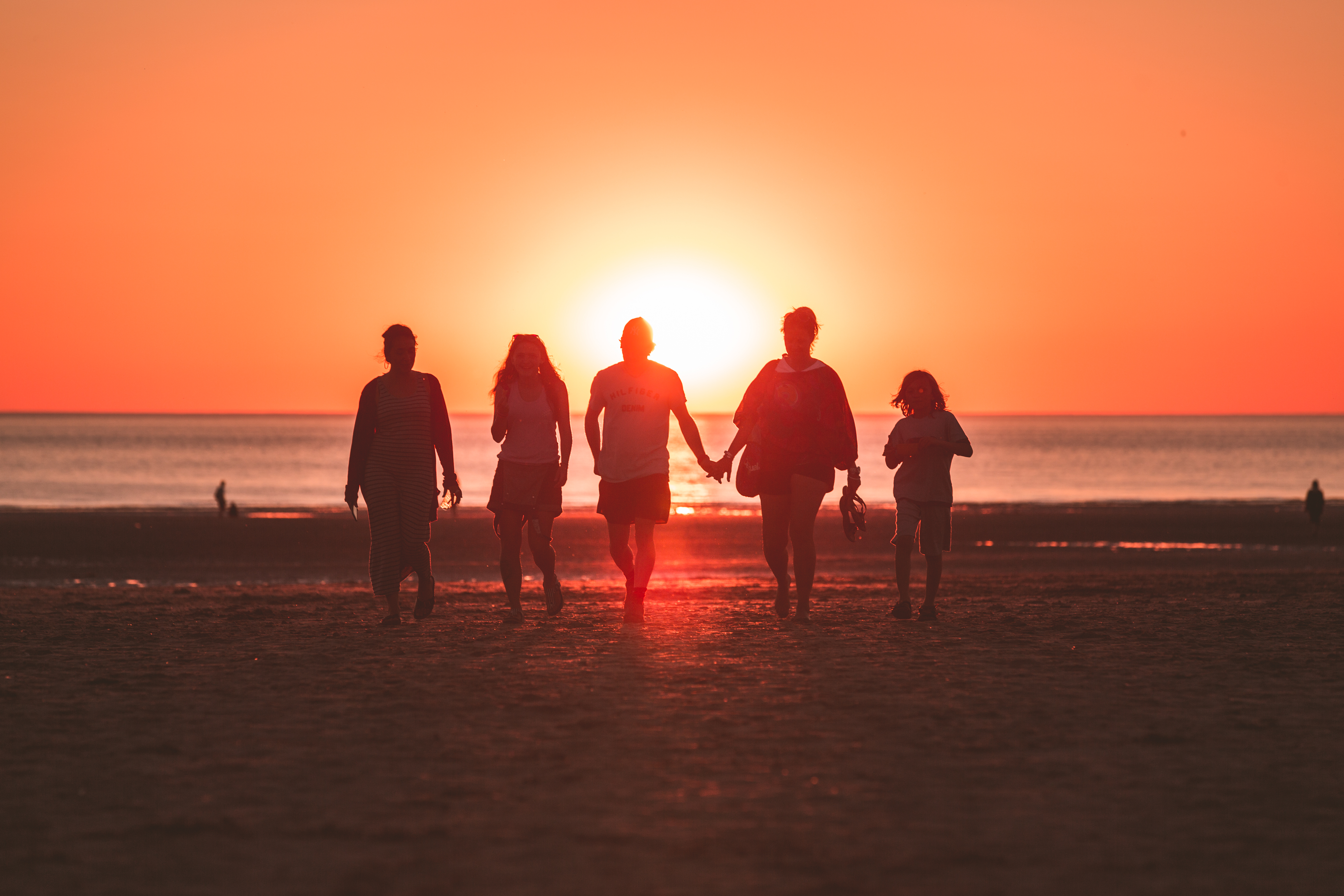 multi-generational travel family mebers walking along the beach at sunset